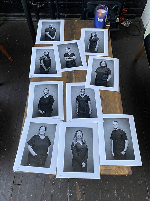 A behind-the-scenes look at Angelo Merendino's printed portraits of nurses on a table.