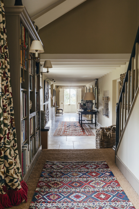 Interior shot of long hall featuring rugs, curtains, and art in Robert Carslaws Cornwall home shot by Anya Rice for Home & Garden magazine