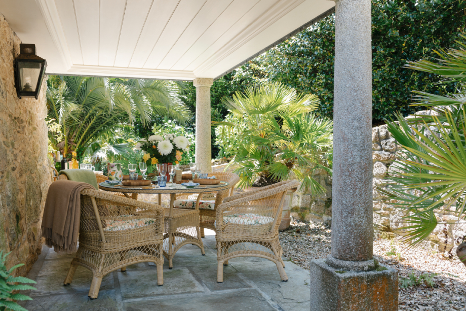 A set table on the sunlit terrace outside of Robert Carslaws Cornwall home shot by Anya Rice for Home & Garden magazine