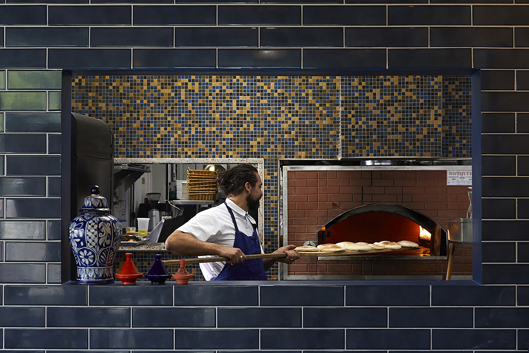 Chef pulling bread from brick oven in kitchen for Atlanta magazine 13 best restaurants shot by Bailey Garrot