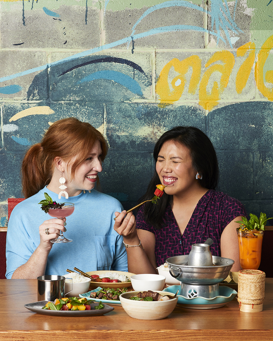 Two women enjoy drinks and food in front of mural at Talat Market for Atlanta magazine 13 best restaurants shot by Bailey Garrot