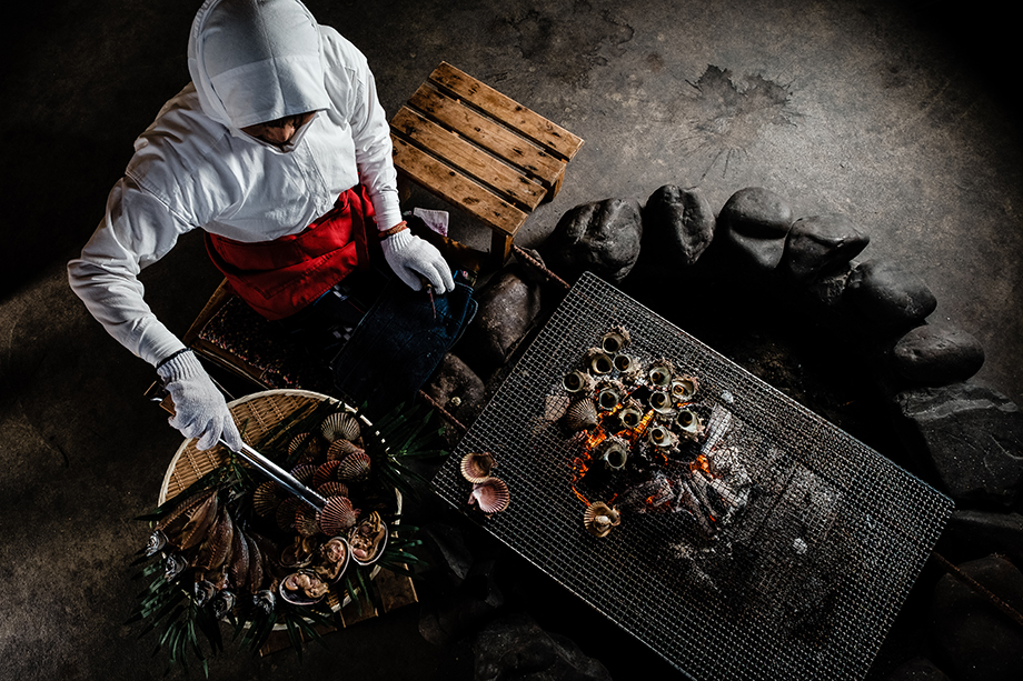Okano Mitsue, age 75, grilling an assortment of shellfish at Ama Hut Hachiman in Toba, Mie Prefecture. Photographed by Ben Weller.