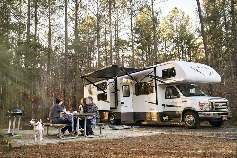 A family sits outside their RV while enjoying the outdoors shot by ben rollins