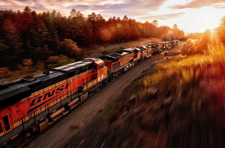 Freight train passing forests at sunset shot by Blair Bunting