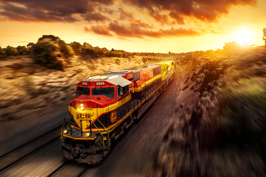 Freight train passing through desert landscape with an orange sky shot by Blair Bunting