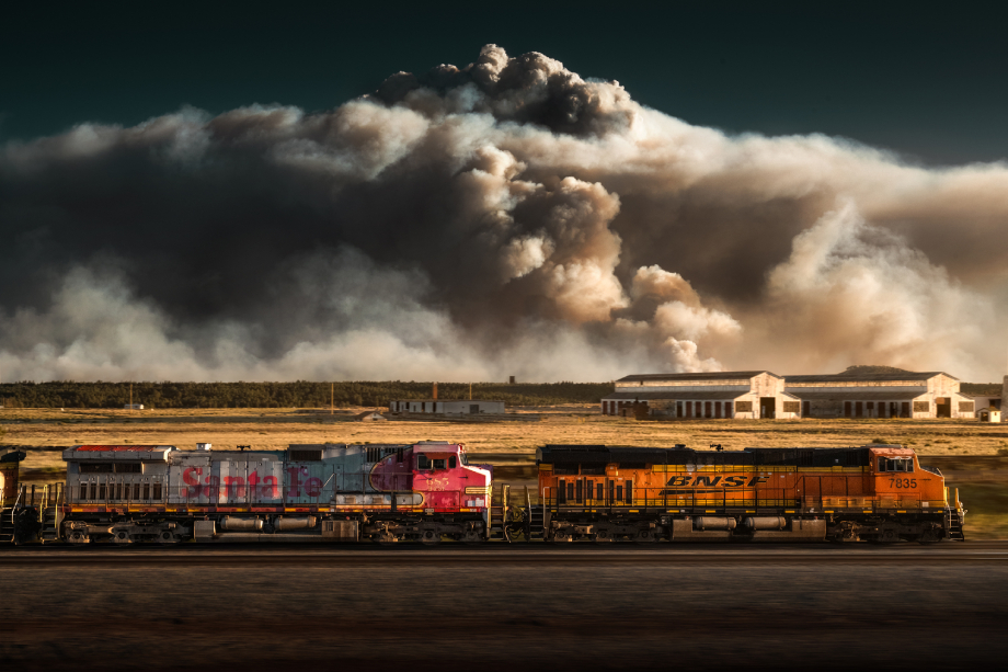 Freight train passing in front of giant cloud of wildfire smoke shot by Blair Bunting