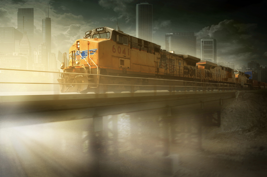 Freight train crossing bridge with city in background shot by Blair Bunting