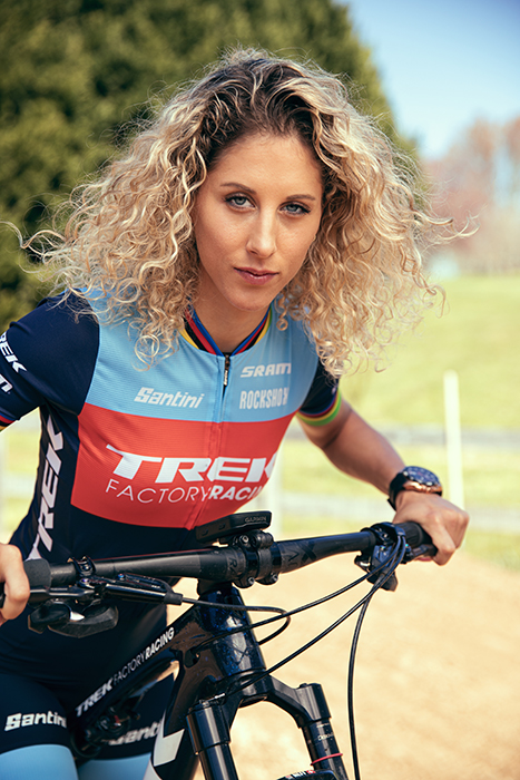 Jolanda Neff looks at the camera while riding her bike. Photographed by Brandon Clifton for Redbull's The Red Bulletin.