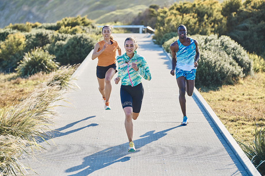 Three runners run in synch while surrounded by lush greenery photograph by Brett Hemmings for Asics