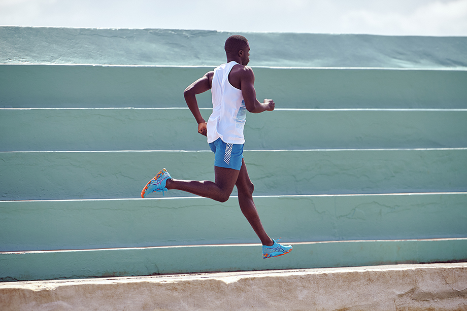 A runner jumps while wearing ASICS color injection sneakers for Brett Hemmings
