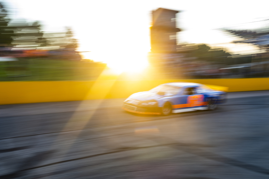 Race car zooms by the car at sunset at Wake County Speedway shot by Bryan Regan for Walter Magazine