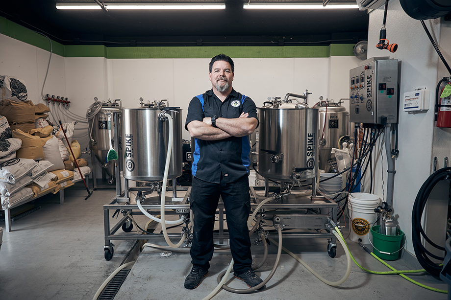 A brewer standing in front of his Spike brewing equipment. Photographed by CJ Foeckler for Spike Brewing.