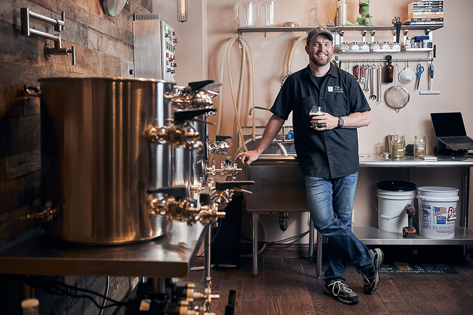 Brewer Greg W. holding a glass of beer in his brewing area. Photographed by CJ Foeckler.