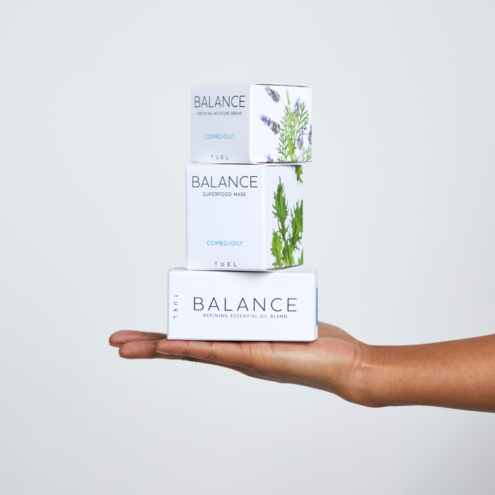 A hand holding three Tuel skincare products featuring Chava Oropesa's ingredient images on product packaging