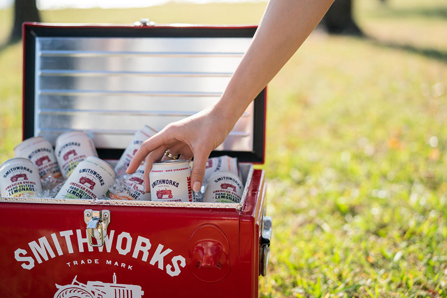 A hand reaches into a cooler to grab a Smithworks Vodka Hard Seltzer Lemonade can captured by Motofish