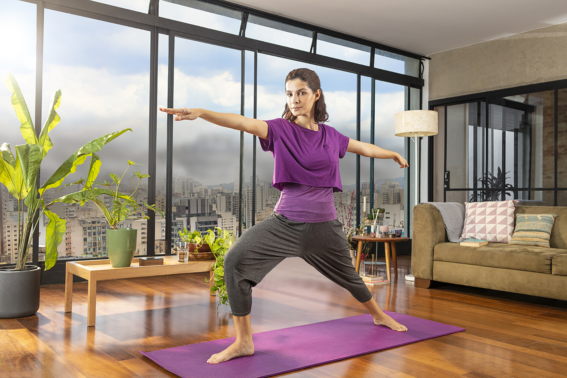 Woman practicing yoga in apartment with large windows with a view of Sao Paulo shot by Claus Lehmann for Allegra