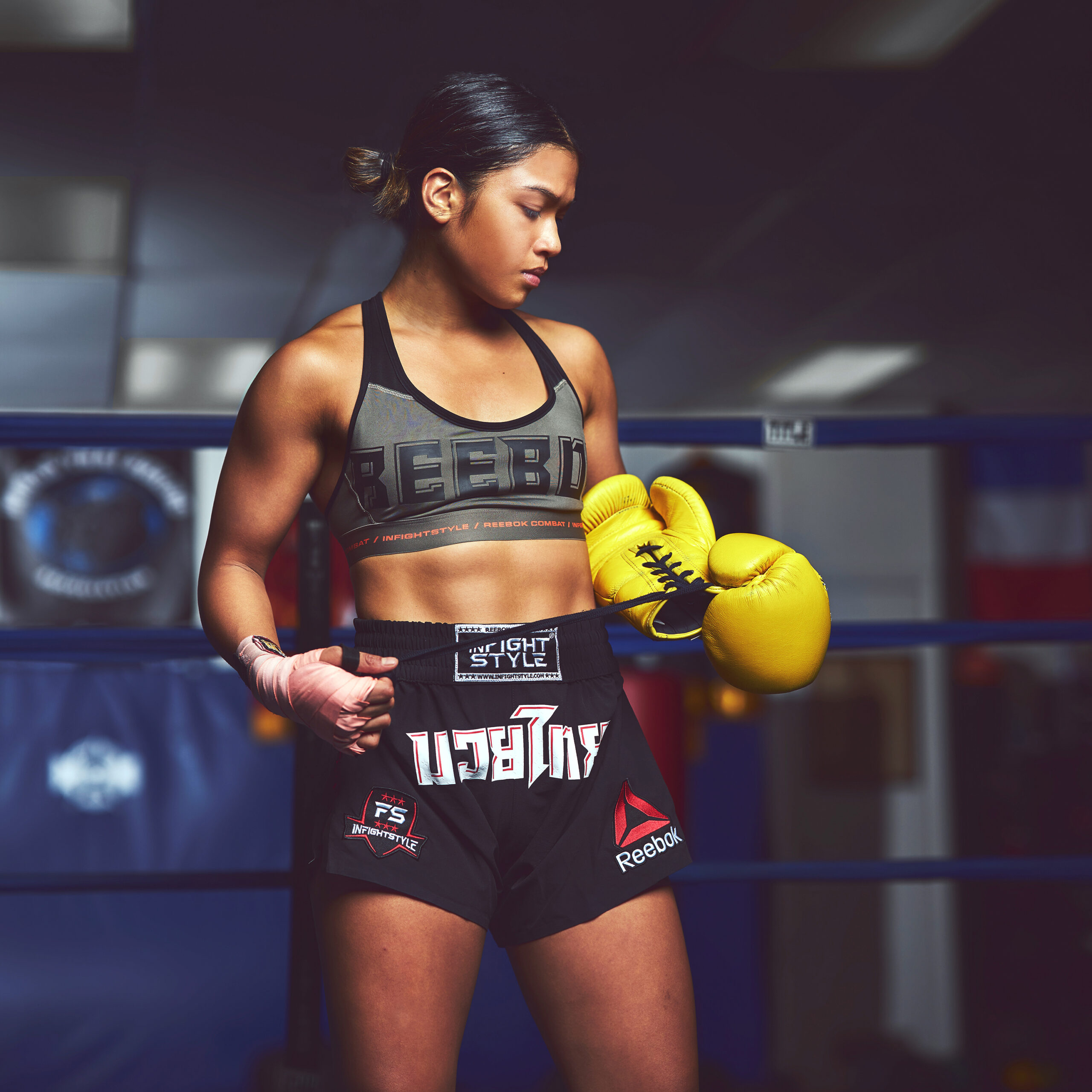 Jeff Dojillo's fighting portrait of Jackie Buntan as she peels her bright yellow gloves off wearing all Reebok and Infightstyle