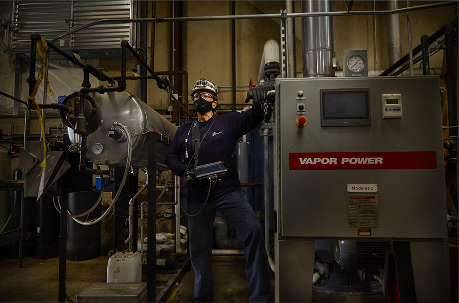 Portrait of a NovaSpect employee at work next to industrial equipment. Photographed by Darren Hauck.