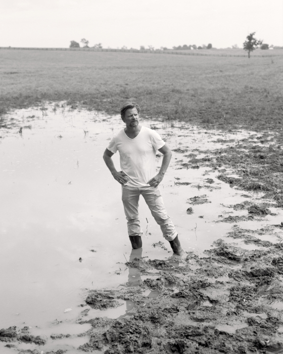 Film portrait of Steve Zahn standing in a muddy field shot by Egan Parks for the Hollywood Reporter