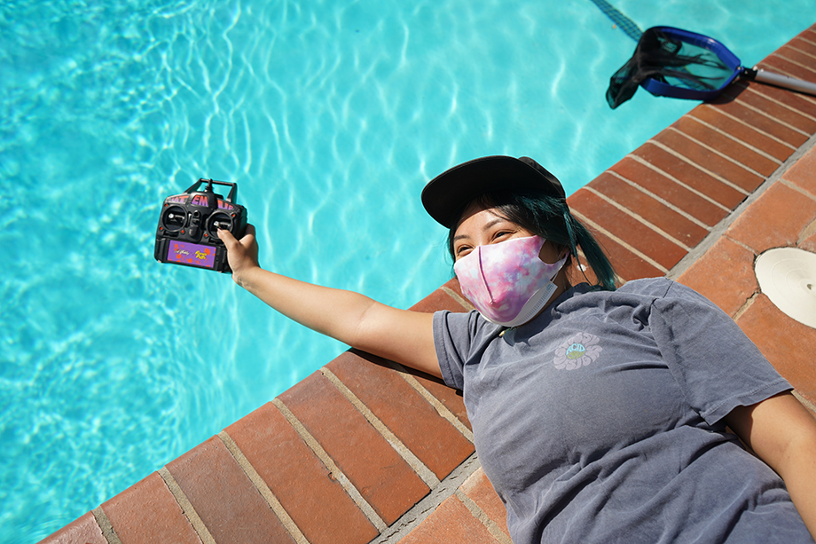 Emily Malan holds the remote control for the small yatch in the pool.