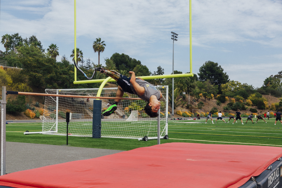 Ezra French jumps over the pole vault shot by Emily Malan for Teen Vogue