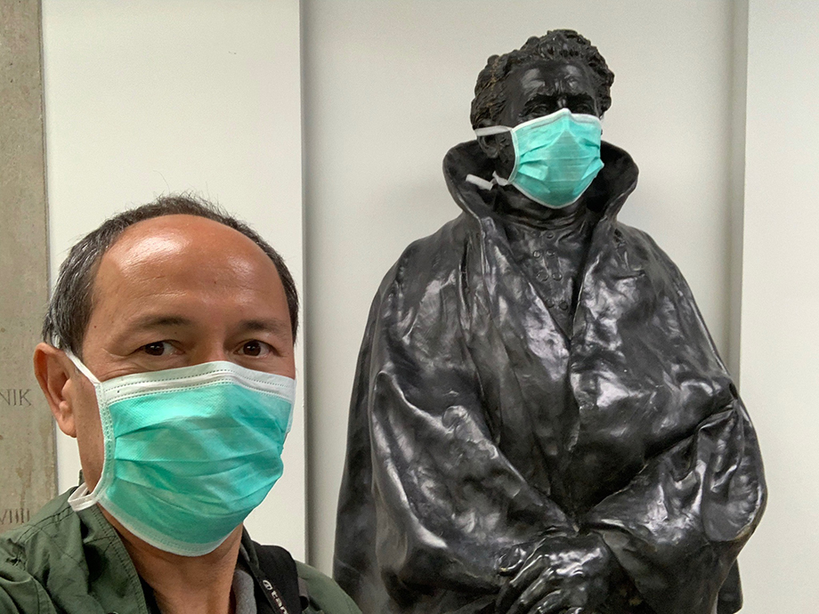 Enno Kapitza wears a mask next to a masked statue.
