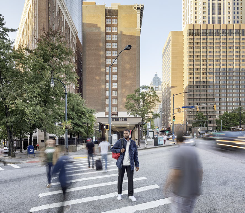 Gregory Miller photographs an outdoor image featuring one of the MARTA rapid transit stations and people walking by.