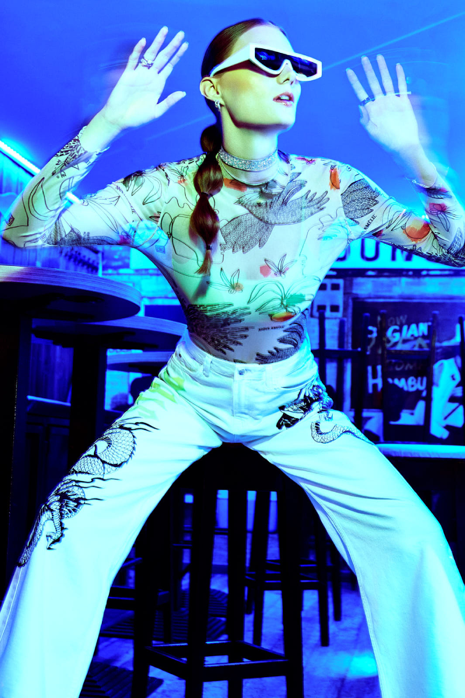 Model Reka Fedra makes light trails with her hands in a blue light bar shot by Illya Ovchar for Glamour Hungary