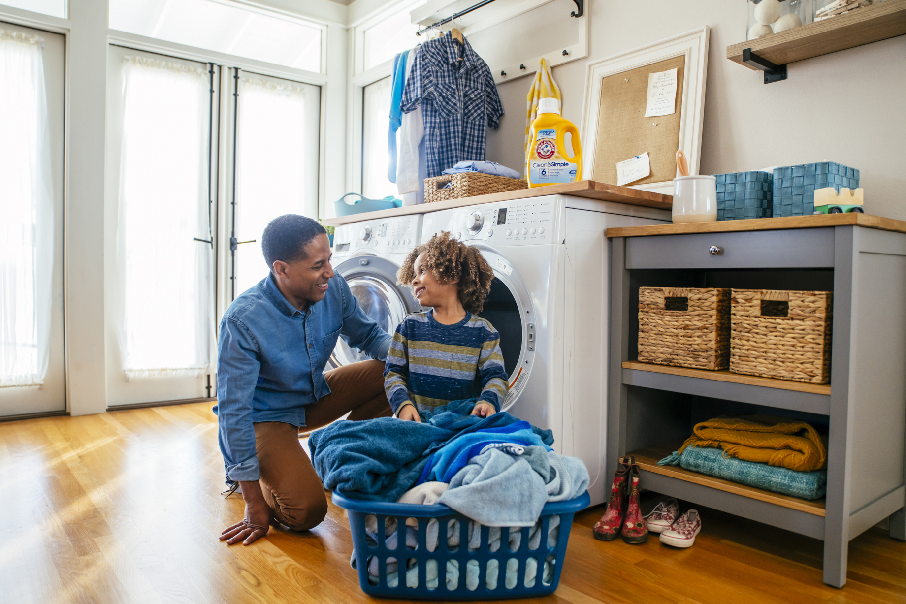 Dad and son doing laundry together with Arm and Hammer Clean and Simple detergent shot by Inti St. Clair