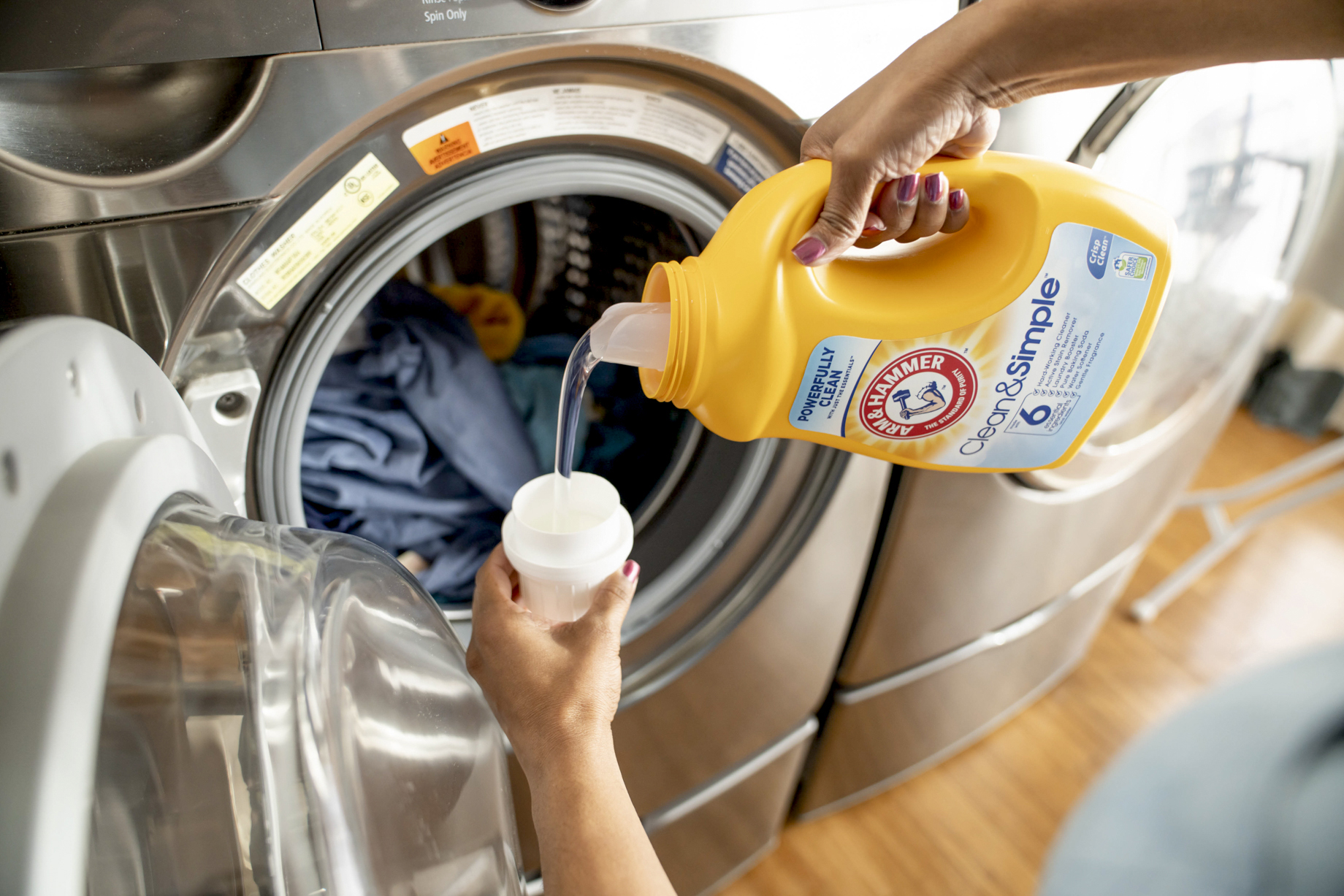 Woman pouring Arm and Hammer laundry detergent by washer shot by Inti St Clair
