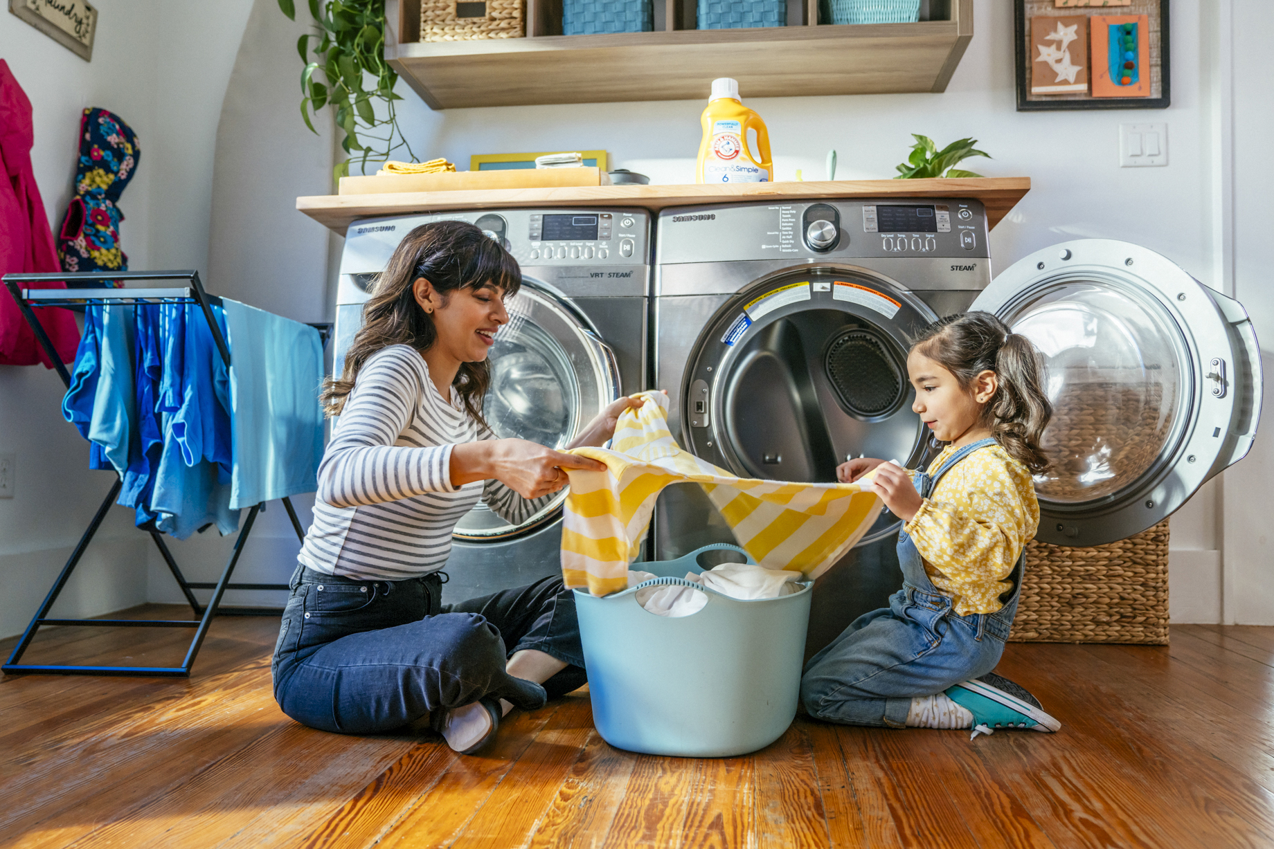 Mom and daughter folding laundry together on floor by dryer shot by Inti St. Clair for Arm and Hammer