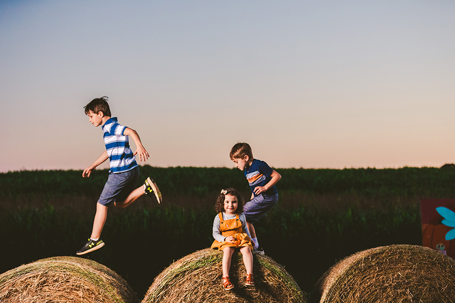 Jack Robert Connolly photographs kids jumping on bales during the 150th anniversary of Denver Downs.