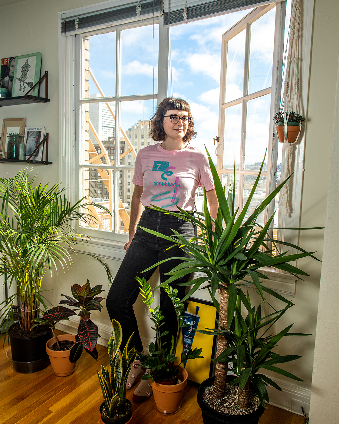 Woman standing by open window amid an abundance of plants shot by Jaime Borschuk for Women at Home project