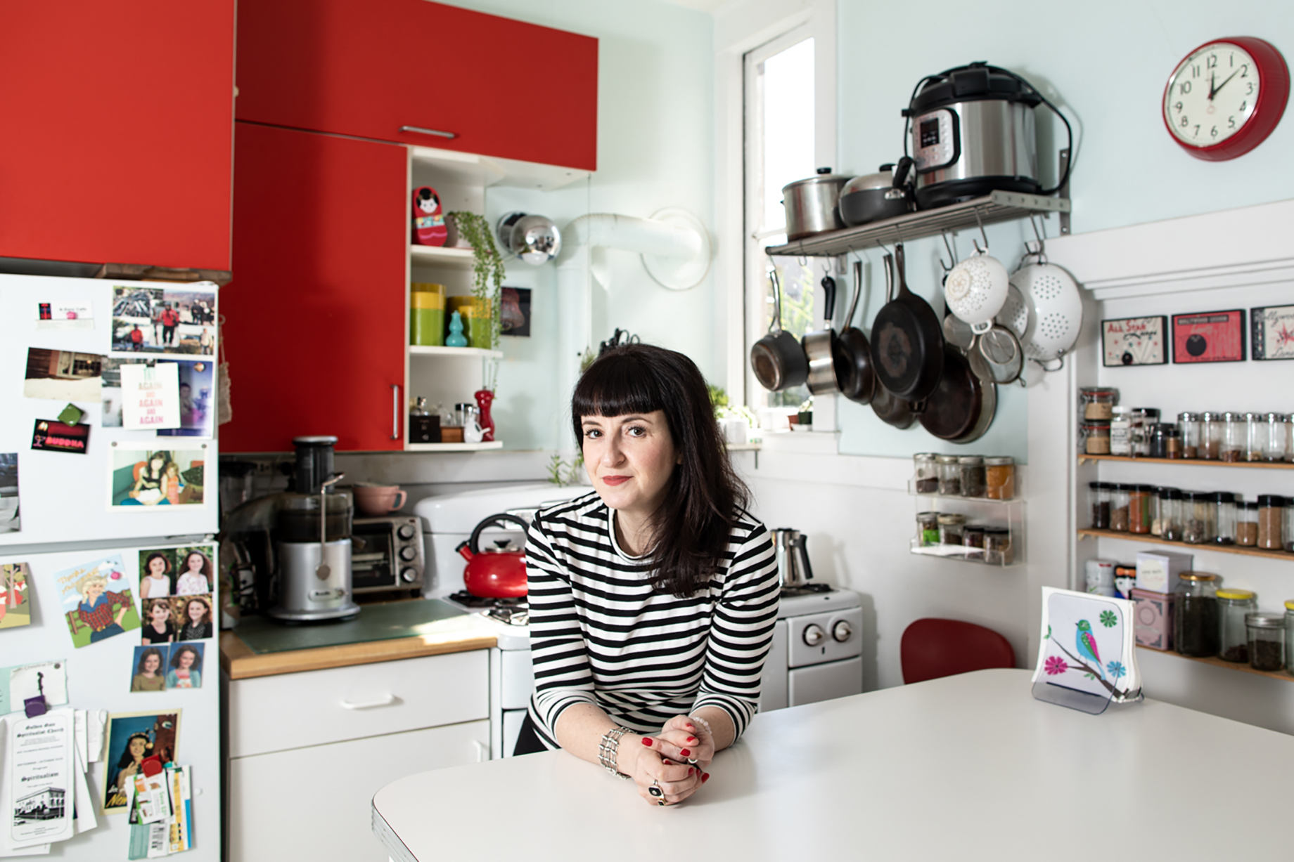 Woman in an organized kitchen with bright red cabinets shot by Jaime Borschuk for Women at Home project
