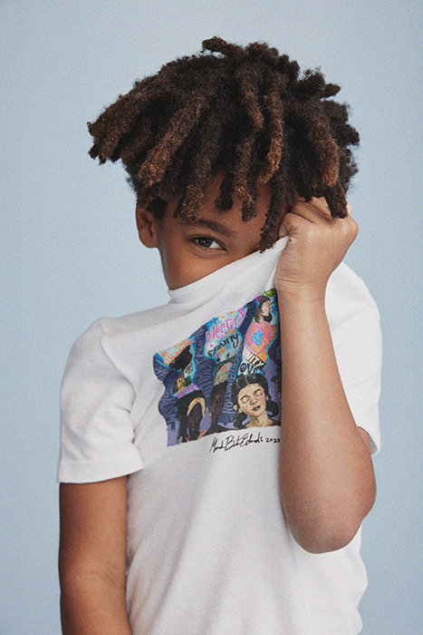A young kid shyly holds up the collaborative t-shirt to his face. Photographed by Janelle Bendycki for Abercrombie Kids.