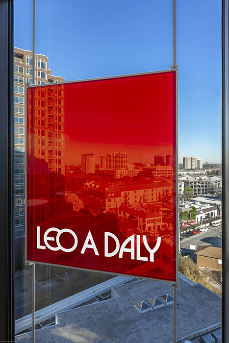 Close up of Leo A Daly's bright sign against the Dallas skyline.