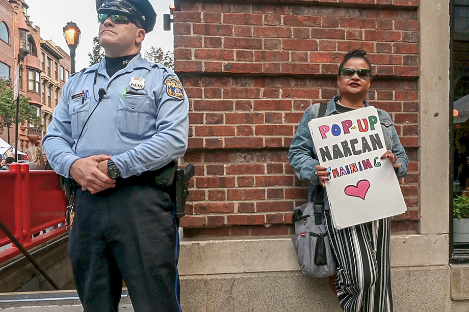 """Roz Pichardo stands next to a police officer while holding up a sign that says """"pop up narcan training."""" Photo by Joe Quint."""