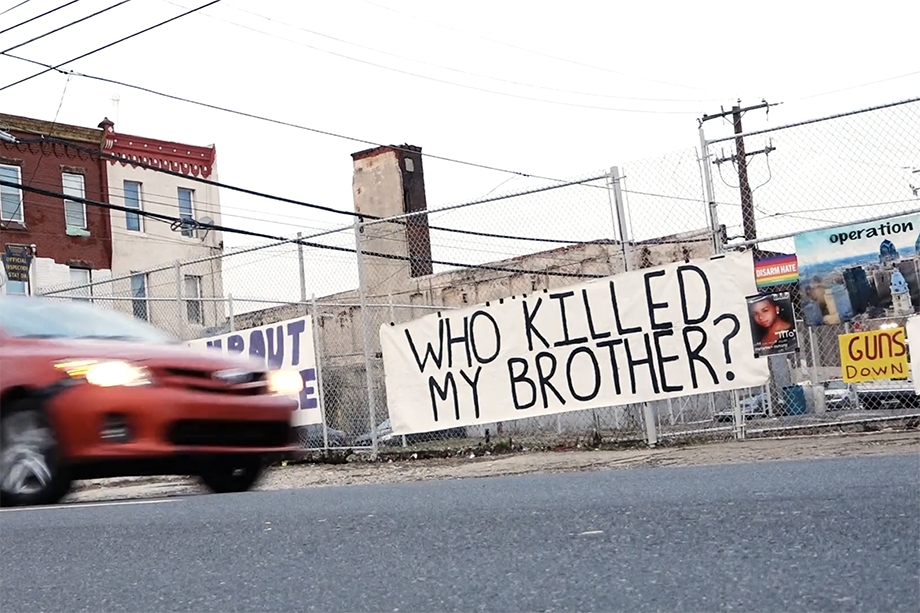 """A sign that reads """"Who Killed My Brother"""" hangs in Kensington during Operation Save Our City's camp out. Photo by Joe Quint."""