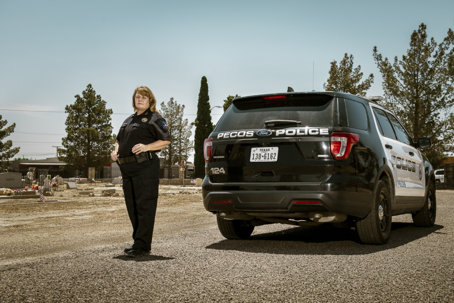 Lisa Durango standing next to her police cruiser at the Fairview cemetery shot by John Davidson for Texas Monthly