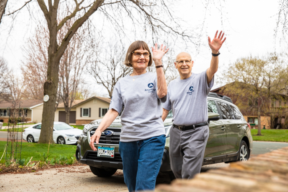 Two AmeriCorps Seniors volunteers waving from their driveway shot by John Davis for AmeriCorps Whats At Your Core Campaign