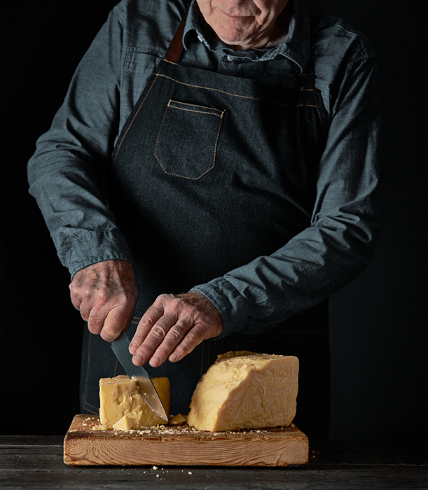 Cheesemonger cuts a block of cheese. Photographed by John Valls for Tillamook Creamery.