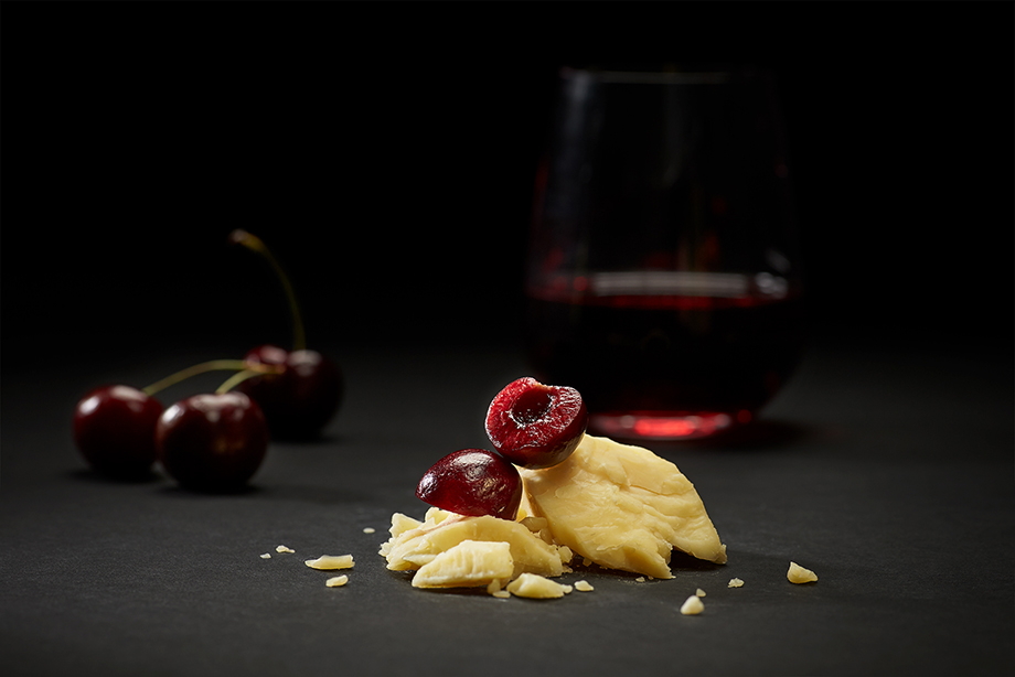 A close up of cheese pairing with cherries. Photographed by John Valls for Tillamook Creamery.