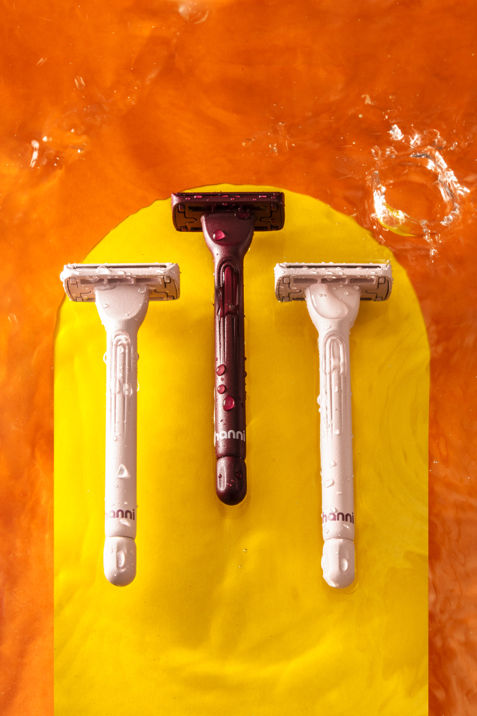 Three Hanni razors submerged in water with splashes on a orange background with a yellow arch shot by Katelin Kinney