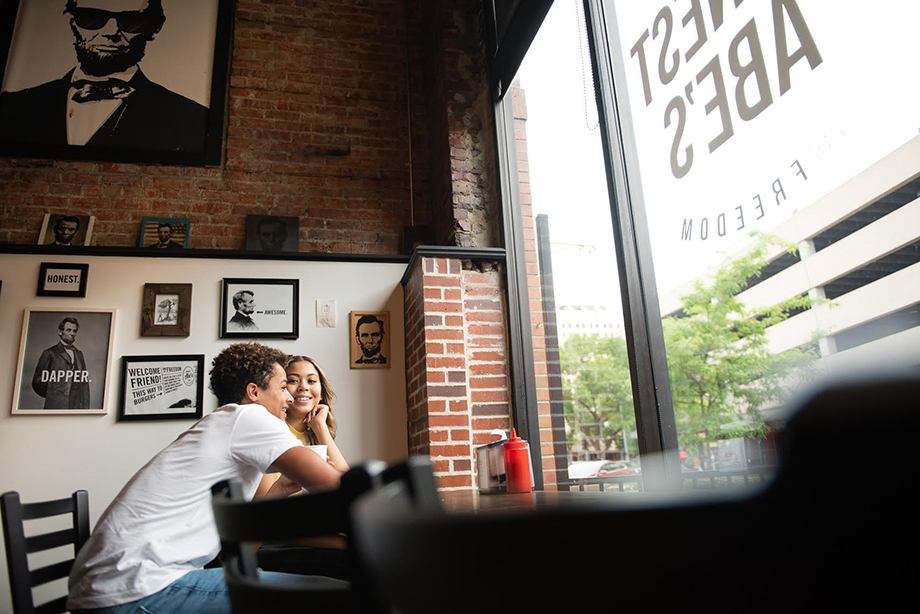 Kobe and Jada on a date at a restaurant in Lincoln, Nebraska. Photographs of Abraham Lincoln adorn the walls. Photographed by Kathy Plunkett for Lincoln Chamber of Commerce and Visitors Bureau.