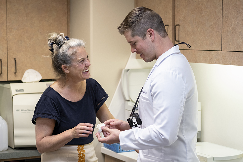Two doctors smile while holding a medical device. Photography by Kevin Titus Photo for Light Wave Dental.