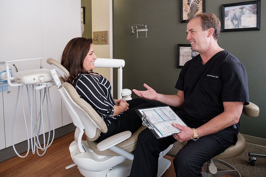 A dentist speaks with a patient. Photography by Kevin Titus Photo.