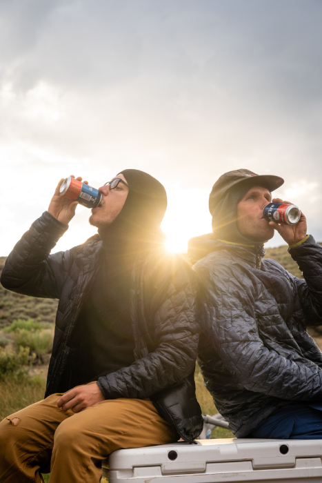 Behind the scenes shot of two men drinking Fat Tire from Kody Kohlman's film C-Team