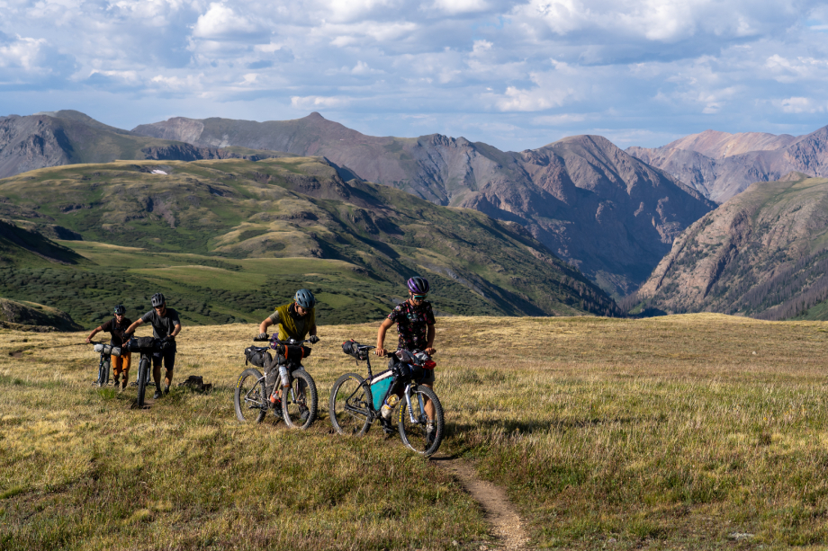 Behind the scenes shot of four men pushing their bikes up a grassy mountain from Kody Kohlman's film C-Team shot for Fat Tire