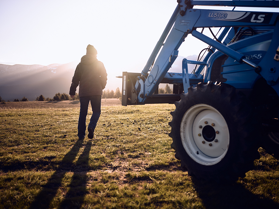 Amy next to a tractor on the ranch. Photography by Kody Kohlman