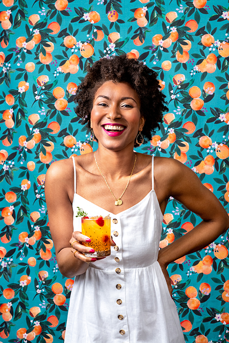 A playful portrait of a woman holding a Clementine Skies. The clementine backdrop and model's matching pink lipstick and nails add pops of color throughout the image.